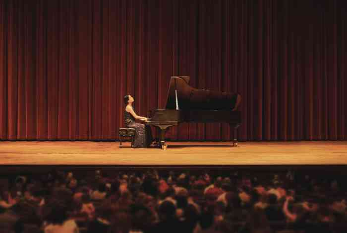a woman playing piano in a concert in front of a large crowd