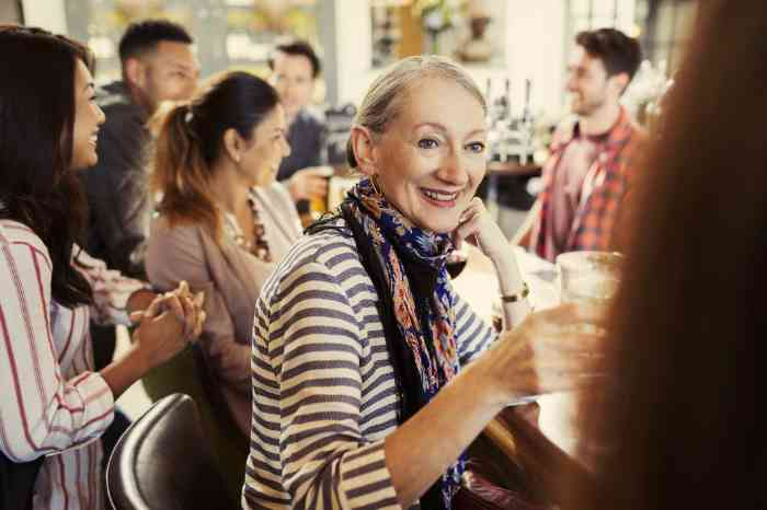 A woman enjoying a drink in a bar thanks to her hearing aid background noise management