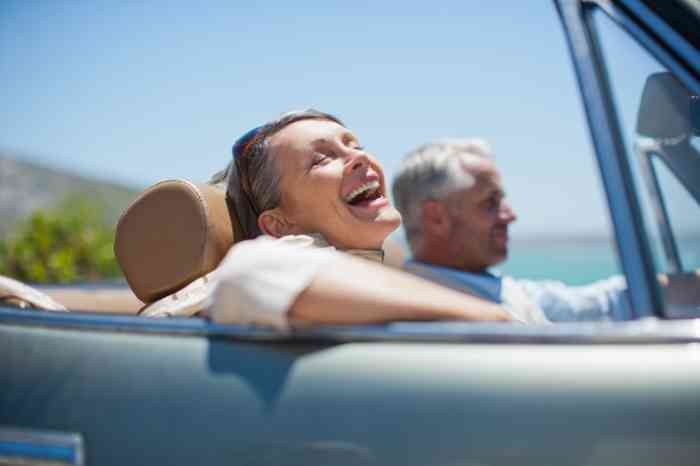 a woman smiling in a car with a man with sea in the background