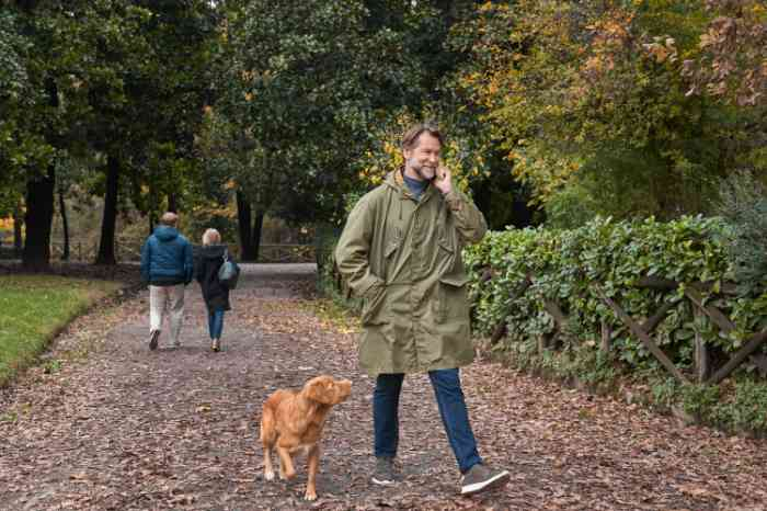 man and dog walking in park