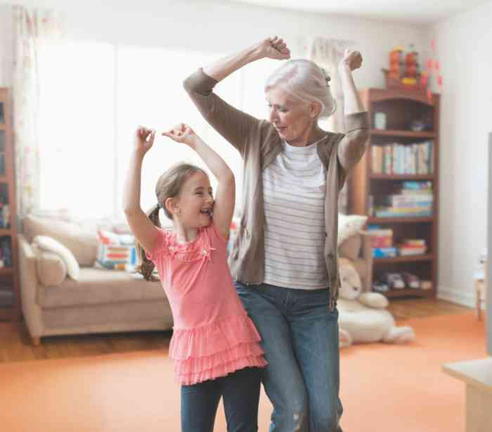 grandmother and little granddaughter smiling and dancing together