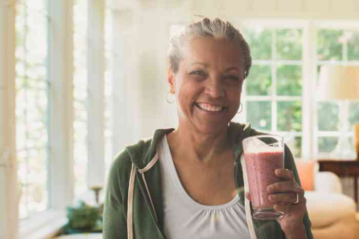 a woman smiling and holding a glass of smoothie in her house
