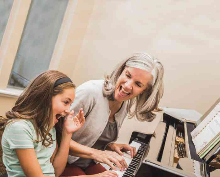 grandmother and granddaughter having fun playing the piano