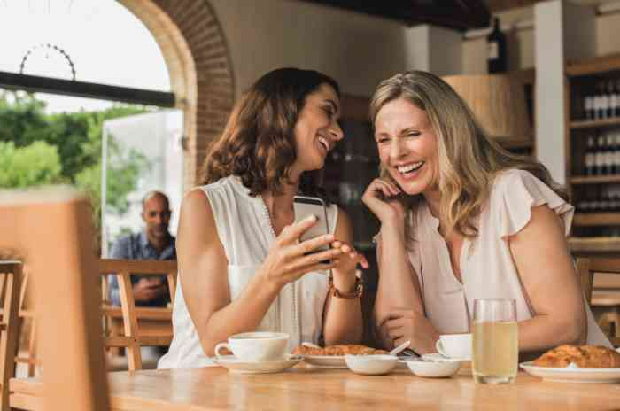 two women chatting together in a restaurant and looking at a mobile phone