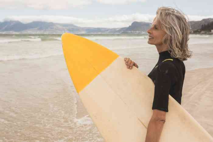 a woman looking at the sea with her surfboard
