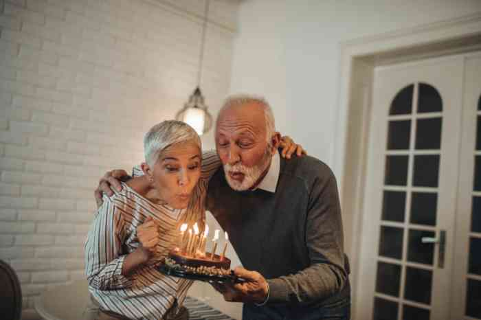 a couple of elderly people blowing out candles on a birthday cake