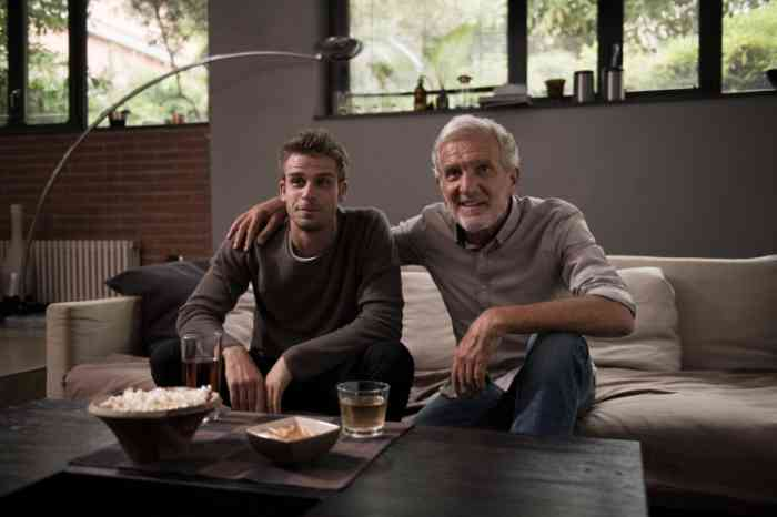 grandfather and grandson watching tv on the sofa with snacks and pop corn