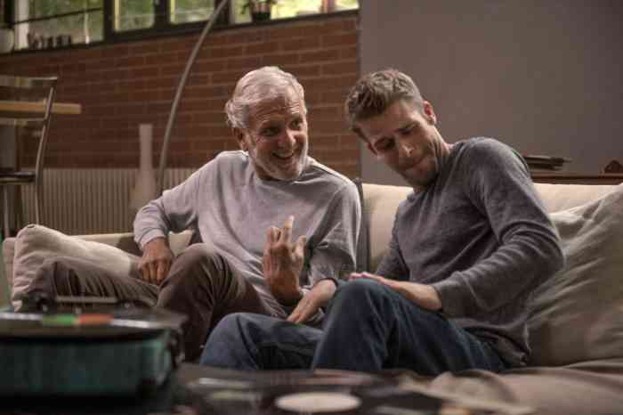 a grandfather and his grandson listening to music on the sofa