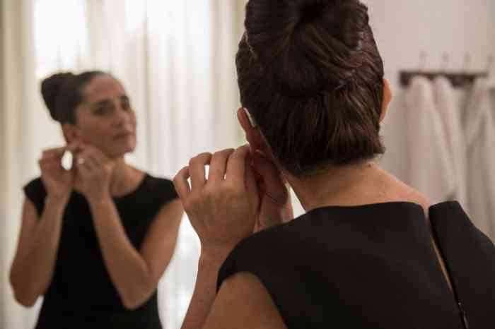 a woman arranging her hearing aid looking herself at the mirror