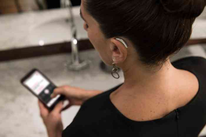 a girl looking at her smartphone connected with her hearing aids