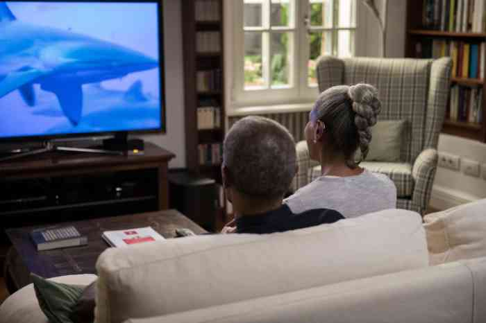 a woman wearing hearing aids and watching a movie with her husband at home