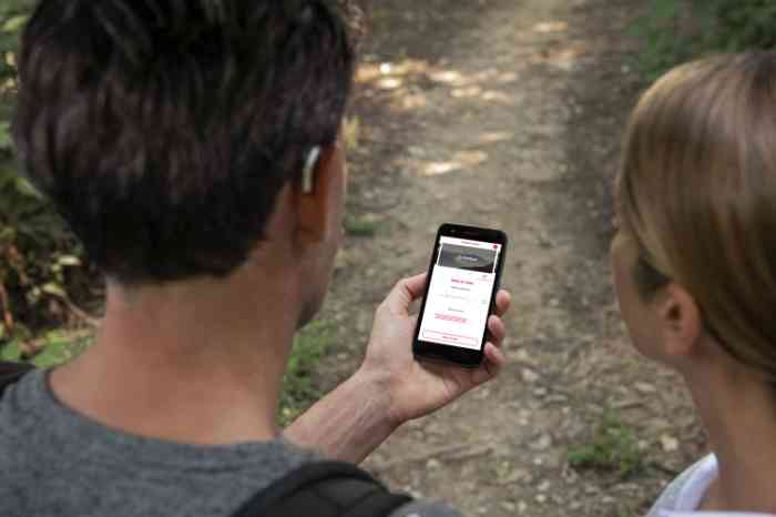 a girl and a man with hearing aids looking at Amplifon app on a smartphone