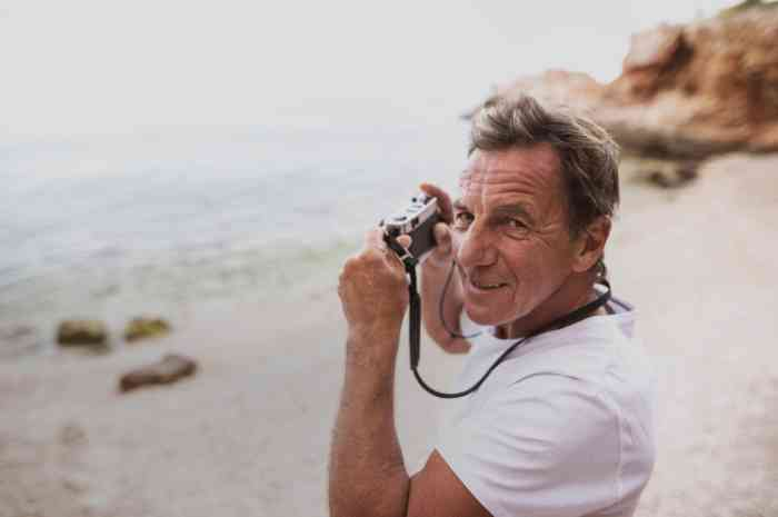 an elderly man taking photo on the beach