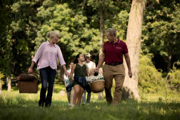 grandparents waling at the park with their granddaughter
