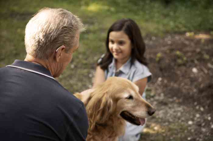 grandfather and granddaughter patting dog