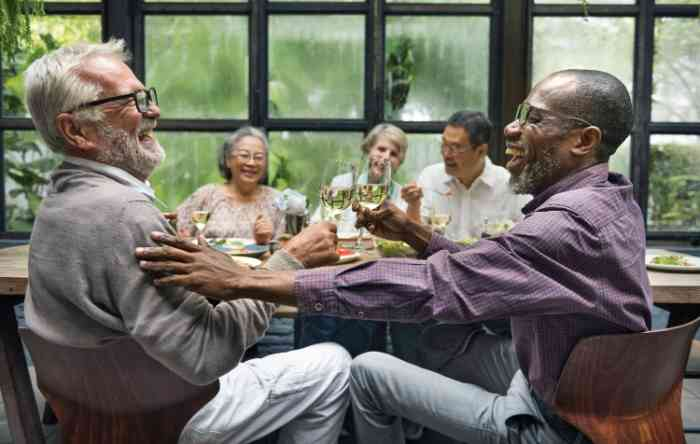 elderly men and women laughing together with glasses of white wine