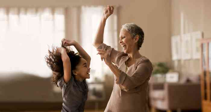 elderly woman and her granddaughter dancing together