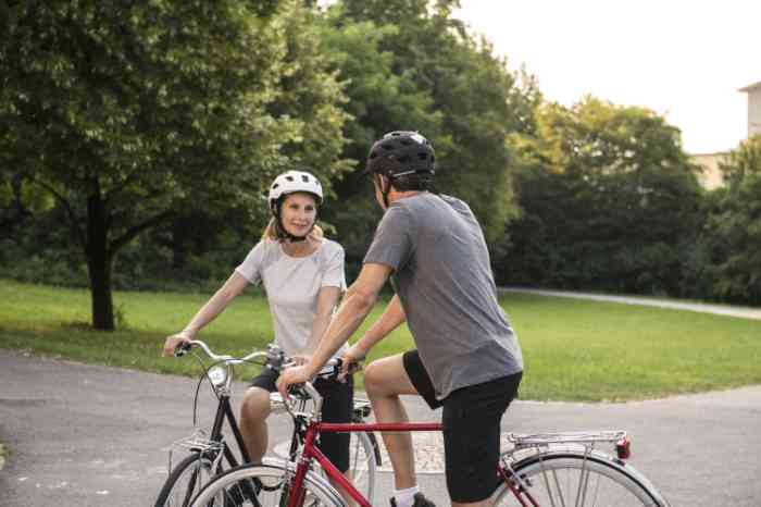two people talking together on their bycicles wearing helmets