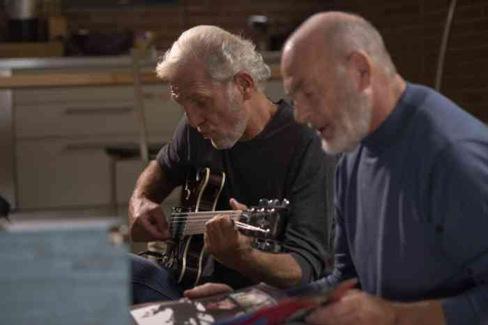 two elderly men playing guitar on a sofa