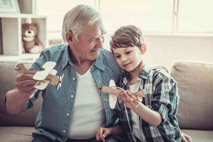 a grandfather and his grandson are playing together with wooden airplanes