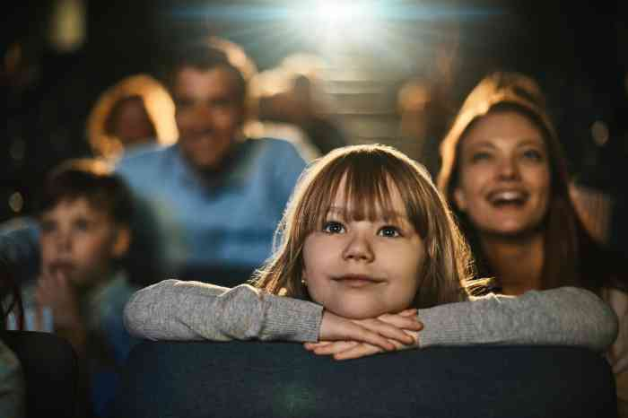 a little girl smiling watching a movie at the cinema