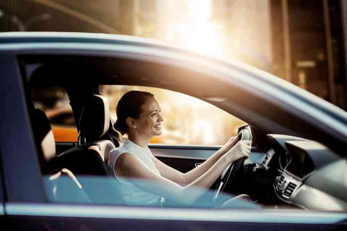 a girl smiling while driving her car
