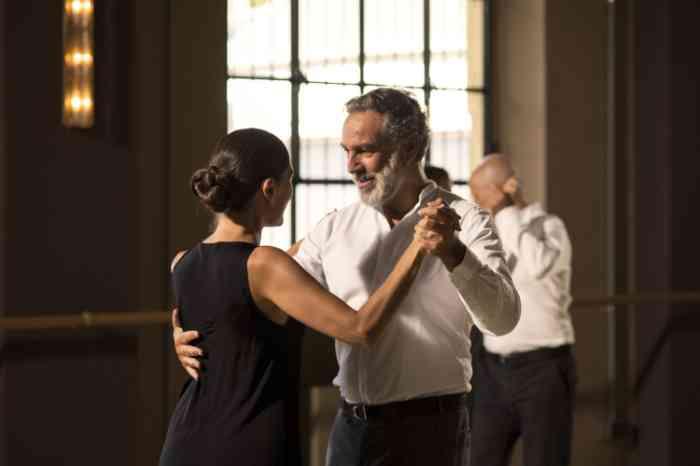 an elderly man and a woman dancing tango