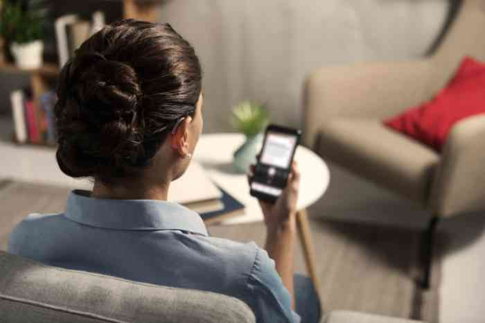 a woman wearing a hearing aid and using a smartphone in her living room