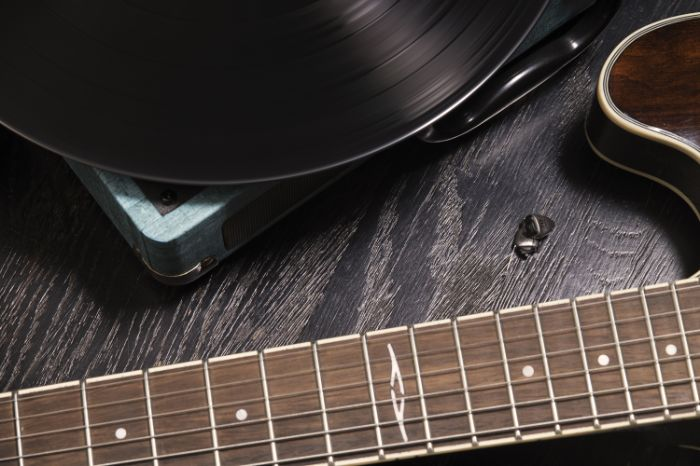 in the ear hearing aid: an invisible hearing aid laid on the floor near a guitar and a vinyl